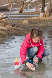 Beauty little girl in rain boots playing with handmade ships in the spring water puddle Stock Photos