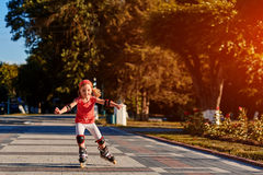 Beauty little girl roller-skating in the city-park in the warm sunshiny summer day. Cute sportive girl dressed in the colorful sportwear. Happy girl holds Stock Photo