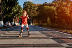 Beauty little girl roller-skating in the city-park in the warm sunshiny summer day. Cute sportive girl dressed in the colorful sportwear. Happy girl holds Royalty Free Stock Image