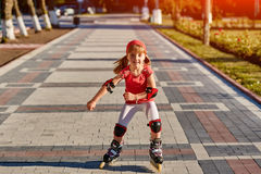 Beauty little girl roller-skating in the city-park in the warm sunshiny summer day. Cute sportive girl dressed in the colorful sportwear. Happy girl holds Royalty Free Stock Photo