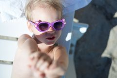 Beauty little girl in sunglasses on the beach royalty free stock photos