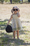 Beauty little girl with sunglasses and a hat. In the park Royalty Free Stock Photos
