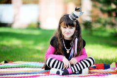 Beauty little princess sitting outdoors on blanket Stock Image