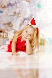 Beauty little Santa girl near the Christmas tree.  Happy girl ce Royalty Free Stock Photos
