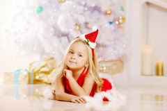 Beauty little Santa girl near the Christmas tree.  Happy girl wi Stock Photos