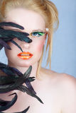 Beauty with long lashes. Beautiful blond woman with exotic feathers and fantasy make-up, long false lashes stock photos