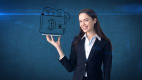 Beauty business woman standing near btc logo. Succesful Bitcoin investment. Concept of virtual criptocurrency. royalty free stock image