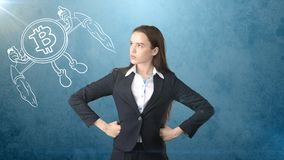 Beauty business woman standing near btc logo. Succesful Bitcoin investment. Concept of virtual criptocurrency. stock image