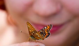 The beauty looks at a beauty. The beautiful girl admires the beautiful butterfly Stock Photography