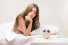 Beauty lying on the bed with a clock Royalty Free Stock Photos