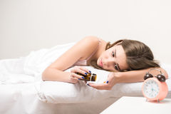 Beauty lying on the bed with a clock and pills. Need some rest. Portrait of young beauty lying in bed and taking pills from insomnia Stock Photo