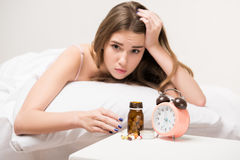 Beauty lying on the bed with a clock and pills Stock Photos