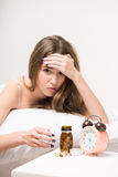 Beauty lying on the bed with a clock and pills Stock Image