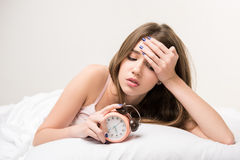 Beauty lying on the bed with clock Stock Photos