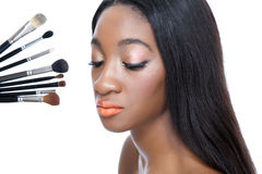 Beauty and make up brushes. Closeup portrait of a young African beauty and make up brushes Royalty Free Stock Photo
