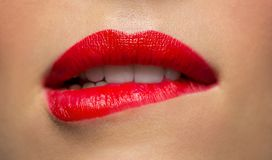 Close up of woman with red lipstick biting lip. Beauty, make up and mouth expression concept - close up of woman face with red lipstick biting lower lip Stock Image