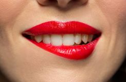 Close up of woman with red lipstick biting lip. Beauty, make up and mouth expression concept - close up of woman face with red lipstick biting lower lip Royalty Free Stock Photography