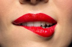 Close up of woman with red lipstick biting lip. Beauty, make up and mouth expression concept - close up of woman face with red lipstick biting lower lip Stock Photos