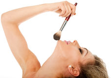 Beauty makeup. Profile of a beautiful female holding a make-up brush Stock Image