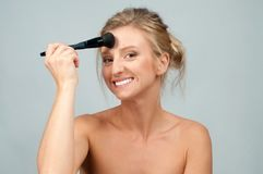 Beautiful woman applying dry cosmetic on the face using makeup brush. Royalty Free Stock Photo
