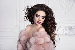 Beauty makeup. Brunette with long curly hairstyle, elegant fashion glamour woman in pink fur coat. Beautiful lady posing in white. Interior royalty free stock image