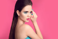 Beauty makeup. Fashion girl portrait. Blue manicured nails. Glam. Our young woman brunette with eye shadow visage and matte lipstick isolated over pink Royalty Free Stock Image