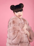 Beauty makeup. Fashion teen girl model in fur coat. Brunette wit. H matte lips and bun hairstyle posing over studio pink background Royalty Free Stock Photo
