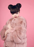 Beauty makeup. Fashion teen girl model in fur coat. Brunette wit. H matte lips and bun hairstyle posing over studio pink background Royalty Free Stock Photography