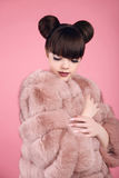 Beauty makeup. Fashion teen girl model in fur coat. Brunette wit. H matte lips and bun hairstyle posing over studio pink background Stock Images