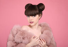 Beauty makeup. Fashion teen girl model in fur coat. Brunette wit. H matte lips and bun hairstyle posing over studio pink background Royalty Free Stock Photos