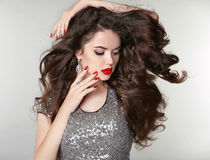 Beauty Makeup. Healthy Long Hair. Beautiful brunette girl with b. Rown curly hair, wavy hairstyle. Manicured nails. Fashion attractive young woman Stock Photos
