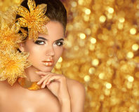 Beauty Makeup, luxury jewelry. Fashion glamour girl model portrait with flowers isolated on golden lights bokeh holiday