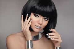 Beauty Makeup, Silver Manicured polish nails. Bob hairstyle. Fas. Hion Style Brunette Woman Portrait with black Short Hair and glitter lips isolated on gray Stock Photo