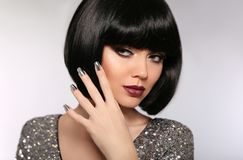 Beauty Makeup, Silver Manicured polish nails. Bob hairstyle. Fashion Style Brunette Woman Portrait with black Short Hair and. Glitter lips isolated on gray stock photography