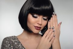 Beauty Makeup, Silver Manicured polish nails. Bob hairstyle. Fashion Style Brunette Woman Portrait with black Short Hair and. Glitter lips isolated on gray stock image