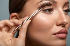 Beauty Makeup. Woman Applying Black False Eyelashes With Tweezer Stock Photo