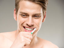 Beauty man. Handsome man cleaning teeth with tooth brush in bathroom Royalty Free Stock Photo