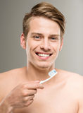 Beauty man. Handsome man cleaning teeth with tooth brush in bathroom Royalty Free Stock Photos