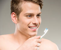 Beauty man. Handsome man cleaning teeth with tooth brush in bathroom Royalty Free Stock Images