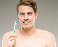 Beauty man. Handsome man cleaning teeth with tooth brush in bathroom Stock Photo