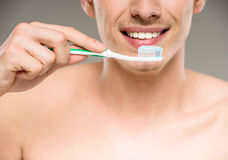 Beauty man. Handsome man cleaning teeth with tooth brush in bathroom Royalty Free Stock Image