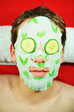 Beauty mask. Man wearing beauty mask and cucumber slices royalty free stock image