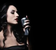 Beauty with a microphone. Picture of a beautiful brunette woman singing stock photo