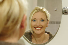 Beauty in the mirror. A lady looking in the mirror, ready for an evening out stock photo