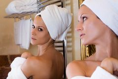 Beauty in the mirror. Beautiful girl looking herself at the mirror royalty free stock image