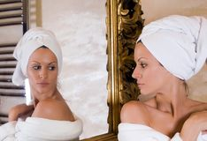 Beauty in the mirror. Beautiful girl looking herslef in the mirror royalty free stock photo