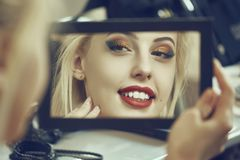 Beauty in the mirror. Portrait of a charming smiling woman admiring herself in the mirror. Beauty makeup, skin care and cosmetics treatment. Shallow depth of Stock Image