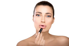 Beauty model applying lipstick to her lips Stock Photo