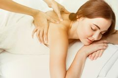 Beauty model with back neck pain massage at spa. Warm tone royalty free stock photos
