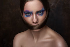 Beauty Model creative Makeup on Eyes and Hairstyle. Beauty Model with blue Makeup on Eyes and creative Hairstyle looking at Camera stock photography